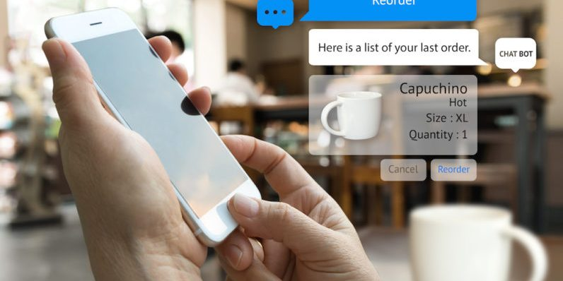 Chat bot and future marketing concept . Customer hand holding tablet for reorder coffee and popup out smart phone screen with automatic chatbot message screen , coffee shop background